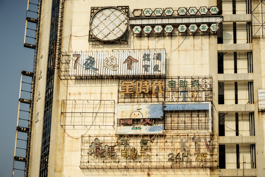 Derelict signs on the outside of the Qiaoyou building in Changhu
