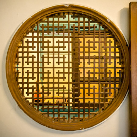 Intricate woodwork on a round window in the Chenggong Hostel