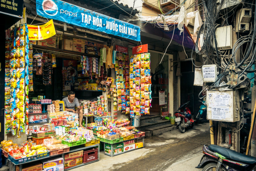 Snack vendor in the alleyways of a dense district west of Hanoi